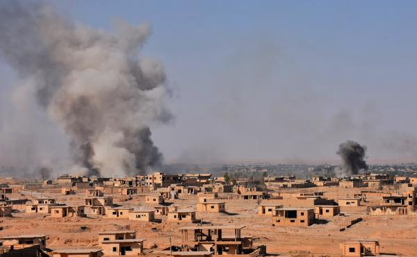 Smoke rises from buildings in the area of Bughayliyah, on the northern outskirts of Deir ez-Zor on Sept. 13, as Syrian forces advance during their ongoing battle against ISIS.