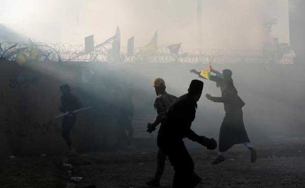 Protesters and militia members throw stones toward the U.S. Embassy in Baghdad on Tuesday.