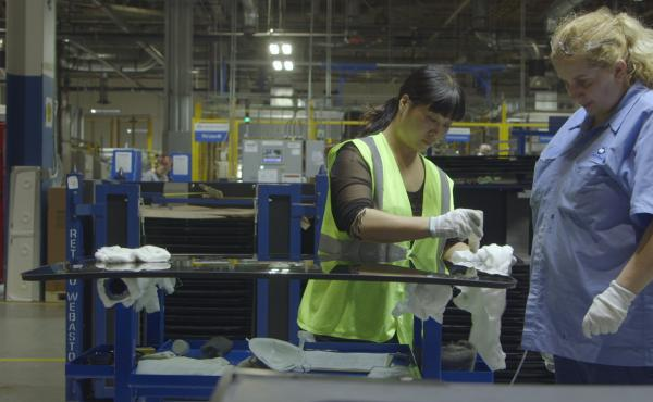 Yuzhu Yang (left) trains Lori Cochran at the Fuyao Glass America factory in Dayton, Ohio, in the documentary American Factory.