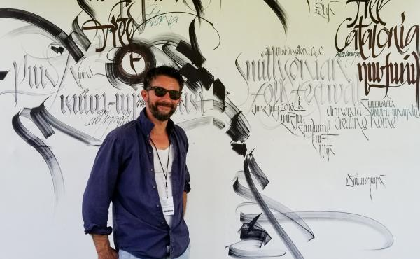 Armenian artist Ruben Malayan stands in front of a poster at his booth at the Smithsonian Folklife Festival in Washington, D.C.