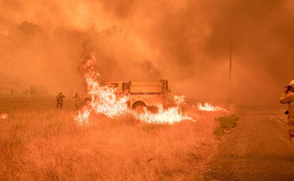 Firefighters scramble to control flames surrounding a fire truck as the Pawnee fire jumps across a highway near Clearlake Oaks, Calif.