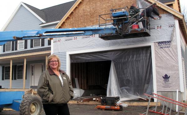 De Desharnais, a homebuilder and real estate agent in Nashua, N.H., stands in front of a house her company is constructing. She says her company had 32 employees at the height of the housing boom, and now only has six despite the industry's gradual recove