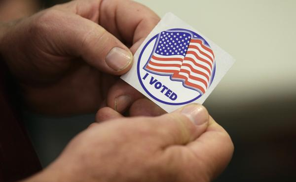 Rick Colyer holds a sticker after placing his vote at the Durham County Library North Regional in Durham, N.C., Tuesday.