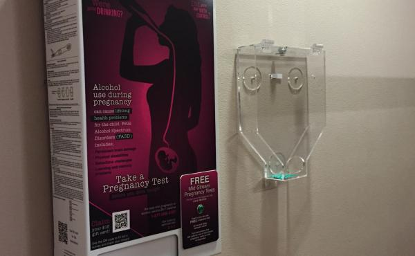 A free pregnancy test dispenser hangs next to a condom dispenser in the women's restroom at the Peanut Farm bar in Anchorage.