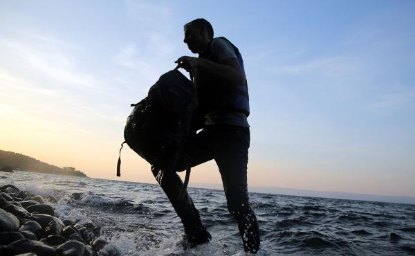 A Syrian migrant who was on a raft from Turkey arrives at the Greek island of Lesbos.