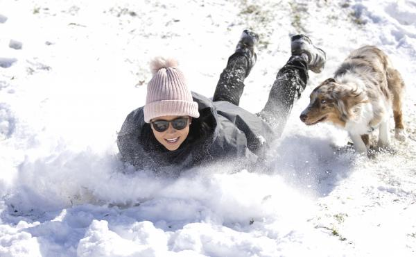 Megan Pennartz and her dog Jensen go sledding in Fort Worth, Texas, on Monday.