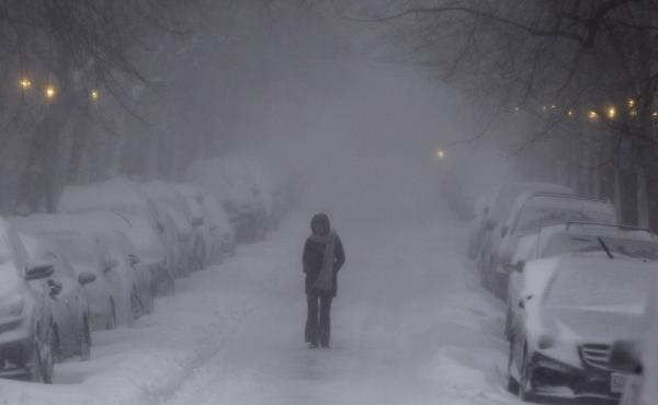 A woman walks in whiteout conditions in Boston on Thursday. Sunday's forecast promises similarly daunting conditions, as a winter storm bears down on the Northeast.