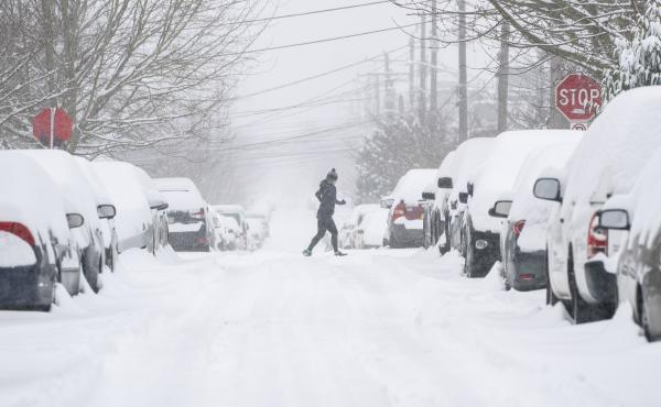 A jogger makes their way across a snowy street on Saturday in Seattle. A large winter storm dropped heavy snow across the region.