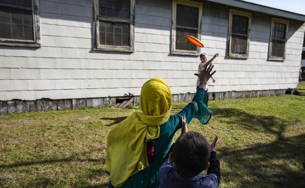 Volunteer Sandra Hoeser plays frisbee with Afghan refugees at Fort McCoy on Sept. 30. There are nearly 13,000 Afghan refugees being cared for at the base under Operation Allies Welcome.