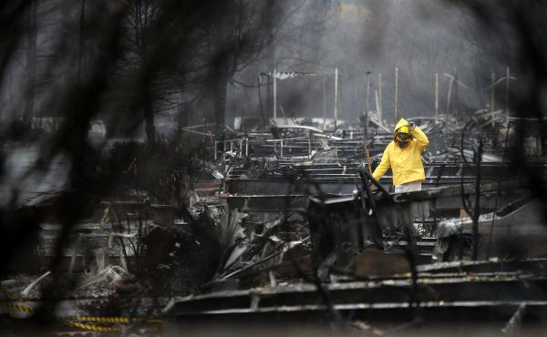 A member of a search and rescue team combs the ruins of a mobile home park Wednesday in Paradise, Calif. Hundreds of people remain missing, and survivors are struggling to cope with life after escaping the Camp Fire.