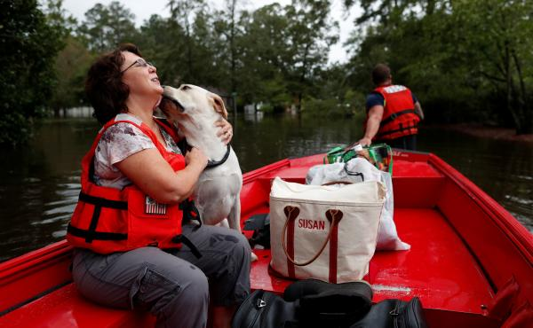 Susan Hedgpeth hugs her dog Cooper Sunday as they go to higher ground via the U.S. Coast Guard in Lumberton, N.C.