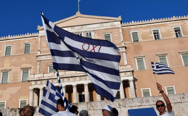 "Protesters hold Greek flags, including one saying ""No,"" during a demonstration at the Greek parliament on July 5, marking the first anniversary of a referendum in which Greeks voted against austerity. Soon after the vote, the prime minister accepted a new"