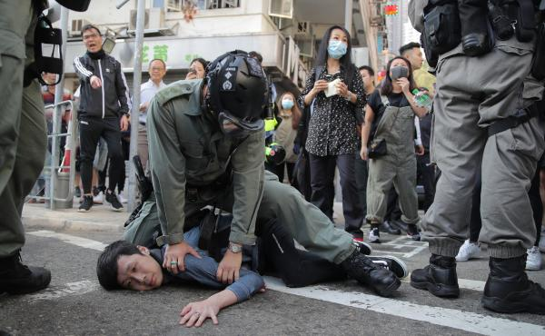 A protester is detained in Hong Kong Nov. 11, 2019. Hong Kong is in the sixth month of protests that began in June over a proposed extradition law and grown to include other grievances.