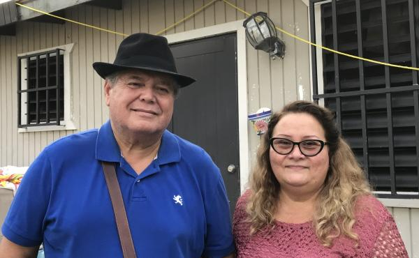 Irma Rivera Aviles and her husband Ivan Martínez stand in front of their home last month. Rivera Aviles was ecstatic about the restoration of power to her neighborhood last Friday.