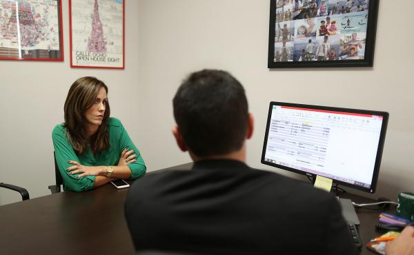 Natalia Mendez goes over mortgage terms with Raul Alvarez, a senior loan officer for Paramount Residential Mortgage Group, Dec. 16 in Miami.