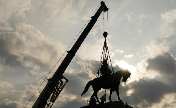 Crews work to remove one of the country's largest remaining monuments to the Confederacy, a towering statue of Confederate Gen. Robert E. Lee on Wednesday in Richmond, Va.