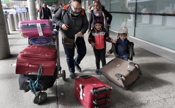 Munther Alaskry, accompanied by his wife Hiba, son Hassan and daughter Dima, gather their luggage as they leave JFK International Airport, in New York City, on Feb. 3. Alaskry and his family arrived after the Trump administration reversed course and said