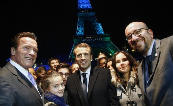 France's President Emmanuel Macron, center, Arnold Schwarzenegger, left, and Prime Minister of Belgium Charles Michel, right, pose for a photo in front of the Eiffel Tower while aboard a boat cruising on the Seine River after the One Planet Summit, Paris,