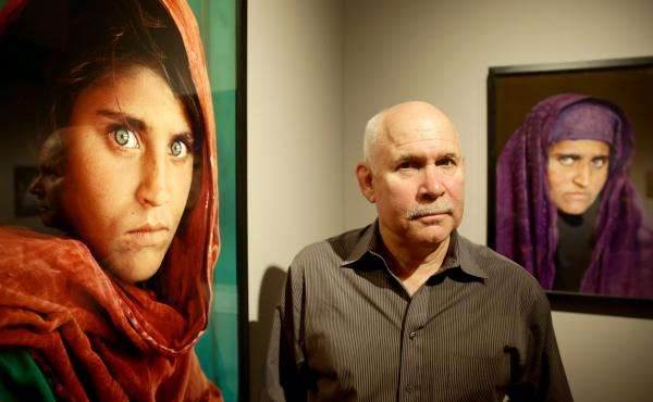 """Sharbat Gula, subject of the famous """"Afghan Girl"""" image, is in a Pakistani jail over alleged ID fraud. In 1984, Gula's brief encounter with photographer Steve McCurry, seen here next to images of Gula, led to a cover photo for National Geographic."""