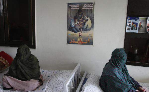 Two women sit, with their faces covered, at a drug treatment center in Kabul, Afghanistan.