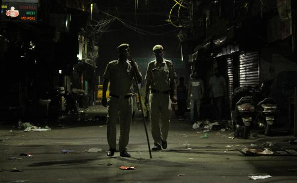 Police officers stand guard during a night curfew designed to limit the spread of the coronavirus in New Delhi. The national capital has imposed a 10 p.m. to 5 a.m. curfew until April 30.