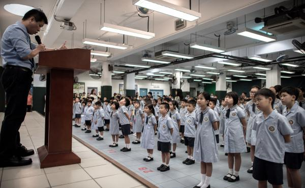 Children stand at attention on the first day of school in Hong Kong in 2015. Education is increasingly becoming a political battleground.