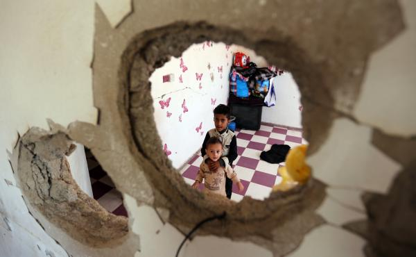 Displaced Yemeni children stare through a hole in the wall of a half-destroyed house in Taez, where they have been staying with several families since violence drove them from their homes in Hodeidah earlier this year.