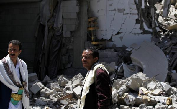 Gunmen loyal to former Yemeni President Ali Abdullah Saleh, stand amid the ruin of Saleh's residence following an airstrike carried out by the Saudi-led alliance in the capital, Sana, on Sunday.