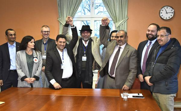Representatives of the Houthi rebel delegation (left) and the Yemeni government's delegation (right) pose for a picture with representatives from the office of the U.N. Special Envoy for Yemen and the International Committee of the Red Cross on Tuesday, d