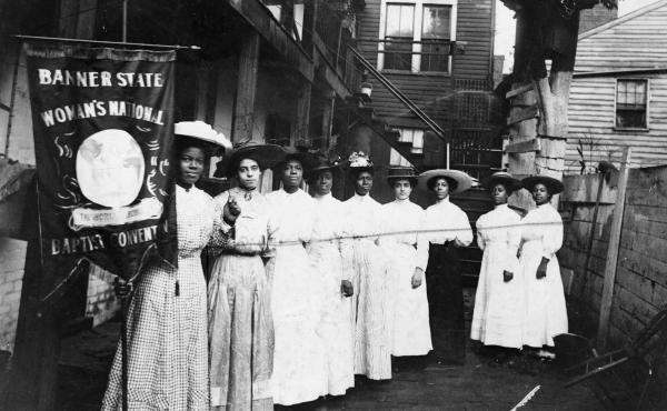 """Nannie Helen Burroughs holds a banner reading, """"Banner State Woman's National Baptist Convention"""" as she stands with other African American women, photographed between 1905 and 1915. Burroughs was an educator and activist who advocated for greater civil r"""