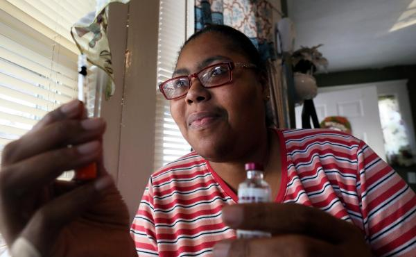 Carmen Smith now gets the insulin she needs via her doctor's prescription. When she lacked health insurance, buying a version of the medicine over the counter was cheaper, she says. But it was hard to get the dose right.
