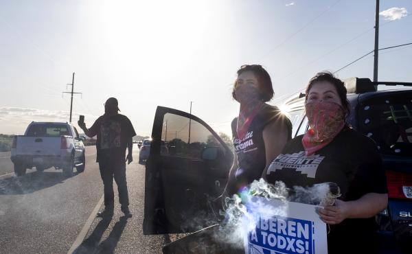 Demonstrators stand along the road in front of the La Palma Correctional Center in Eloy on April 10, 2020. The event was one of several car rallies calling for the release of immigrants detained at the ICE facility during COVID-19.