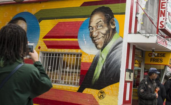 People walk past a mural of comedian Bill Cosby on the side of Ben's Chili Bowl restaurant in Washington, D.C., Dec. 31, 2015.
