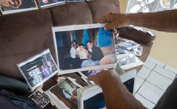 Jose Torres's rearranges some of the photos he was able to save in his home.