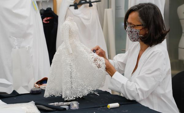 An employee sews a miniature dress in Dior's sewing workshop in Paris on July 4. This year Dior created a miniature collection for its haute couture show and presented it as a film.