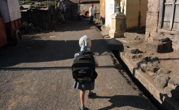 A child leaves for school in a village in India. Last November, the Indian government announced new rules limiting the weight of school bags depending on a child's age. But the rules are not always enforced.