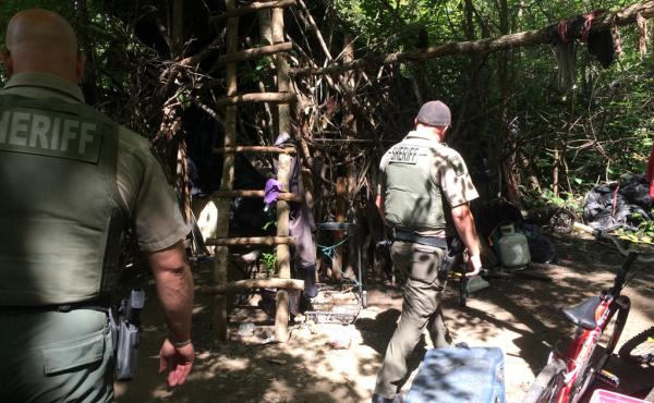 "During their patrol of the Bear Creek Greenway, Jackson County Sheriff's deputies walk through a years-old encampment that deputies call ""the Hobbit House."""