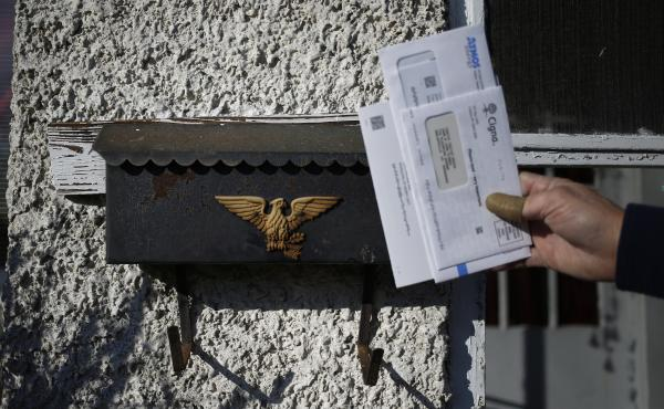 A U.S. Postal Service letter carrier delivers the mail in Shelbyville, Ky. A White House task force recommended ending the mailbox monopoly held by USPS.