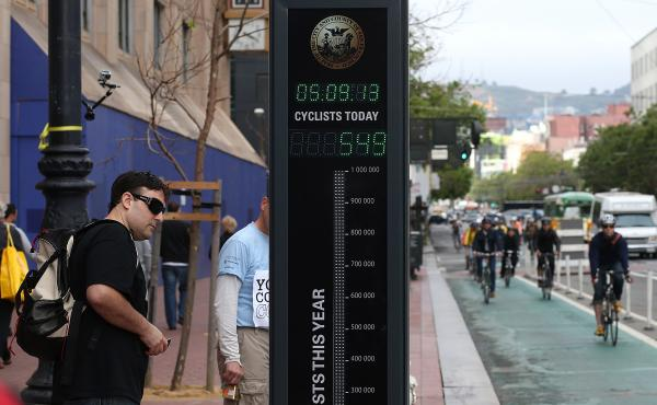 A pedestrian stops to look at an automated real-time bike counter on Market Street in San Francisco.