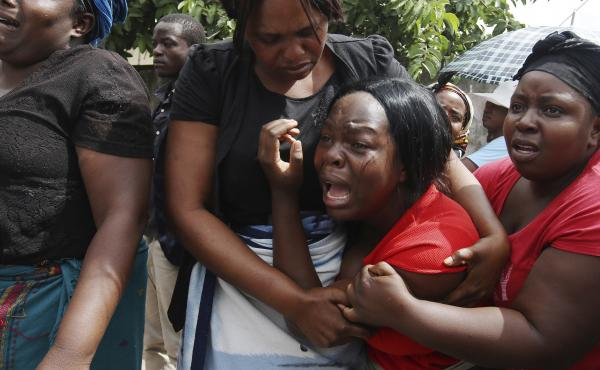 A family member of Kelvin Tinashe Choto reacts, during his funeral in Chitungwiza, about 30 kilometres south east of the capital, Harare, Zimbabwe on Saturday. The 22-year-old was shot in the head, one of at least a dozen people killed in a violent crackd